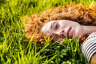 Portrait of redheaded young woman lying on meadow - p300m2028979 by Jo Kirchherr