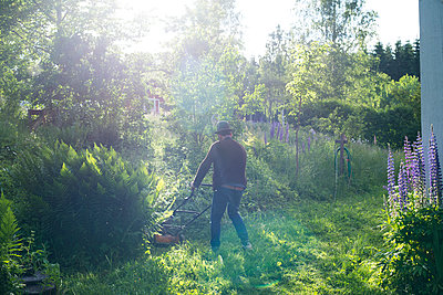Man mowing lawn in backyard - p312m1113807f by Johan Willner