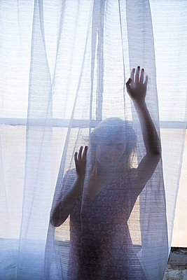 Young woman standing behind the blinds by the window  - p794m1476497 by Mohamad Itani