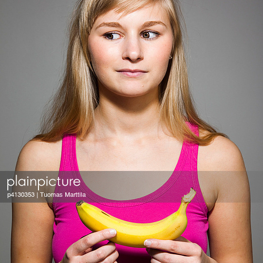 Young woman with banana - p4130353 by Tuomas Marttila
