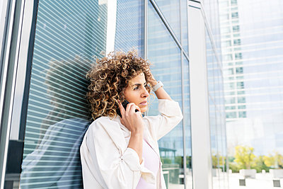 beautiful woman with curly hair talking on her smartphone - p1166m2255061 by Cavan Images