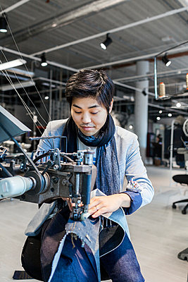 Male fashion designer using sewing machine in jeans factory - p1185m994339f by Astrakan