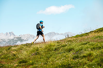 Mature sportsman trail running in the mountains on meadow - p300m2242918 by Manu Prats