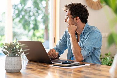 Contemplating male freelancer with laptop looking away while sitting at home office - p300m2276506 by Steve Brookland