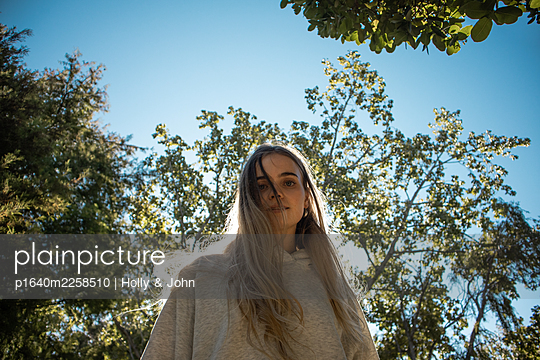 Teenage girl with blond hair in a park - p1640m2258510 by Holly & John