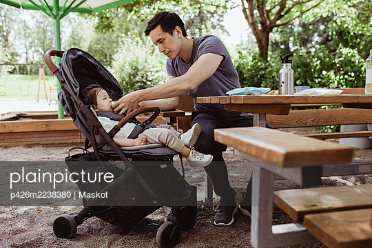 Father feeding baby son while sitting in playground - p426m2238380 by Maskot