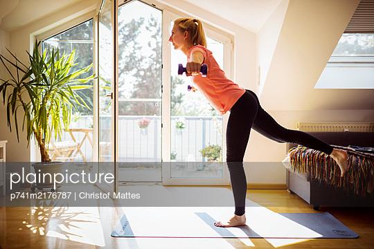 Junge Frau beim Hanteltraining in ihrer Dachwohnung - p741m2176787 von Christof Mattes