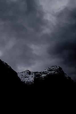 Snow-capped mountain range under dark clouds - p1057m2168565 by Stephen Shepherd