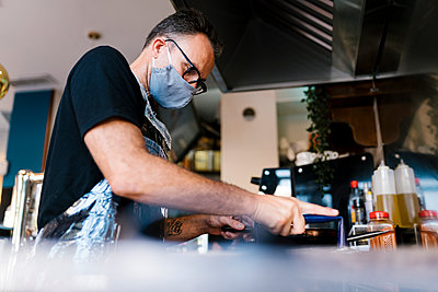 Male barista wearing face mask while cooking in kitchen of coffee shop during COVID-19 crisis - p300m2220708 by Ezequiel Giménez