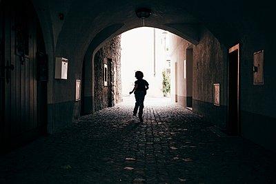 Rear view of boy running through tunnel, Bludenz, Vorarlberg, Austria - p429m1105759 by JFCreatives