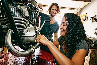 Man watching woman repairing motorcycle in garage - p555m1303788 by Peathegee Inc