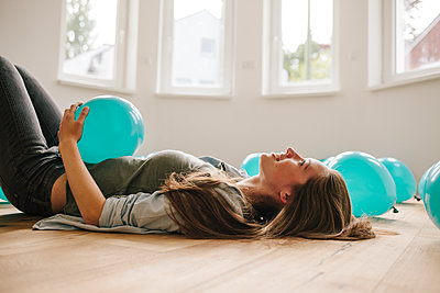 Young woman in new apartment with balloons - p586m1064899 by Kniel Synnatzschke