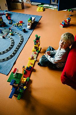 Junge spielt mit Spielzeugeisenbahn - p819m1128377 von Kniel Mess