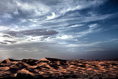 Desert landscape with sand dunes under a cloudy sky. - p1100m1482277 by Mint Images