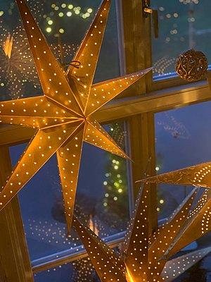 Christmas star hanging in window - p1166m2129883 by Cavan Images