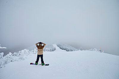 Snowboarder looking at view from peak of mountain - p343m1447128 by Josh Campbell