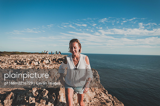 Young woman on cliff looking out over ocean in summer in Portugal - p1166m2216729 by Cavan Images