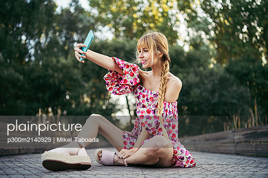 Portrait of smiling young woman  sitting on boardwalk in summer taking selfie with smartphone - p300m2140929 by Mikel Taboada