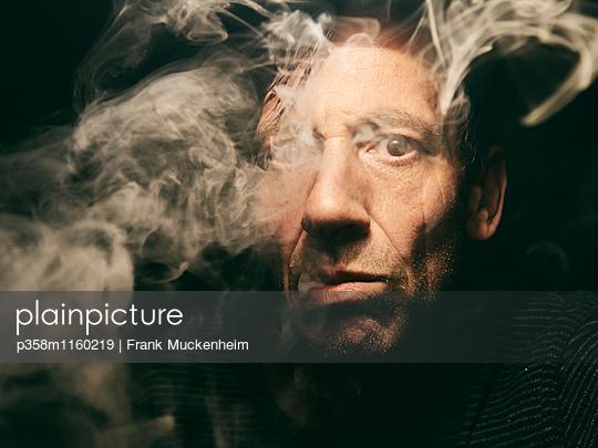 Mann beim Rauchen  - p358m1160219 von Frank Muckenheim