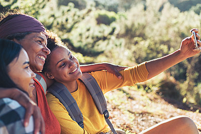Happy mother and daughter hikers taking selfie with camera phone - p1023m2135891 by Trevor Adeline