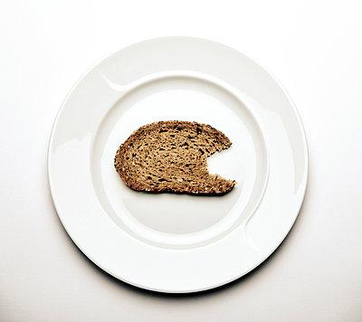 Scheibe Brot auf Teller - p1221m1025817 von Frank Lothar Lange