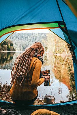 Frau mit Kaffee sitzt vor ruhigem Bergsee - p1455m2204908 von Ingmar Wein