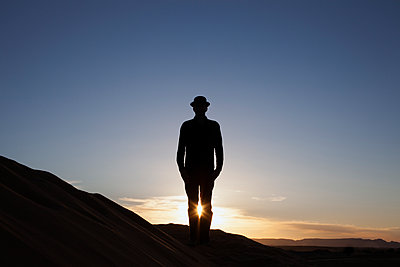 Morocco, Merzouga, Erg Chebbi, silhouette of man wearing a bowler hat standing on desert dune at sunset - p300m2104386 by Petra Stockhausen