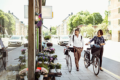 Business people with bicycles walking on sidewalk in city - p426m1196692 by Maskot