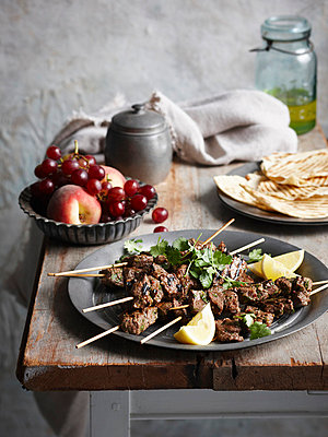 Plate of lamb skewers with lemon - p429m727192 by Brett Stevens