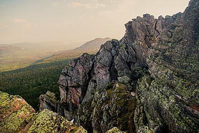 Rocky hillside over remote landscape - p555m1411145 by Aleksander Rubtsov