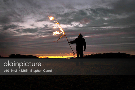 Man holding burning branch - p1019m2148265 by Stephen Carroll