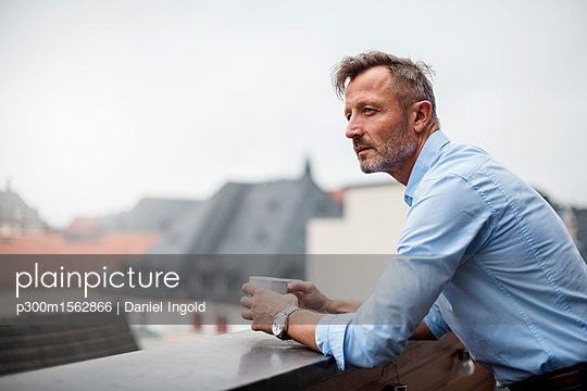 Portrait of mature businessman with cup of coffee on roof terrace - p300m1562866 by Daniel Ingold
