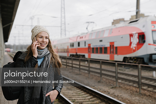 Portrait of smiling young woman on the phone waiting on platform, Vilnius, Lithuania - p300m2155214 by Hernandez and Sorokina