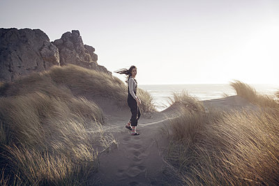 Portrait of woman standing at beach against clear sky - p1166m1210486 by Cavan Images