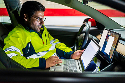 Mature technician programming on laptop while sitting in electric car - p300m2242501 by Javier De La Torre Sebastian