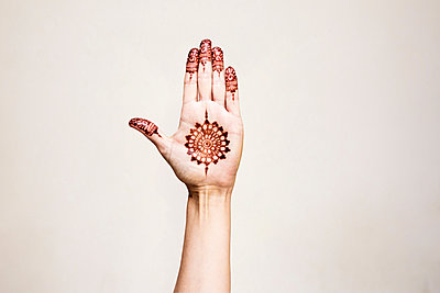 Hand with henna tattoo making gesture - p429m2075439 by Tom Dunkley