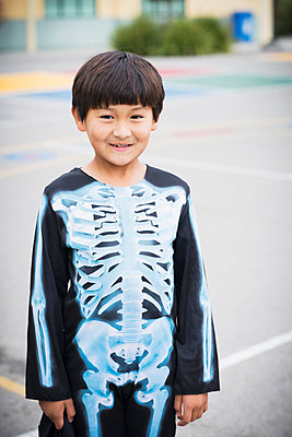 Portrait of Hispanic boy smiling in skeleton costume - p555m1419098 by Sollina Images