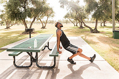 Black man leaning on picnic table in park stretching leg - p555m1522893 by Kolostock