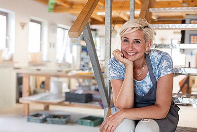 Portrait smiling artist on steps in studio - p1023m1194296 by Agnieszka Olek