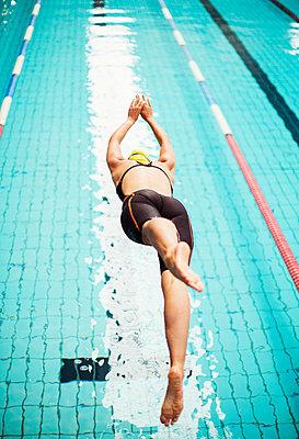 Swimmer diving into pool - p1023m923622f by Paul Bradbury