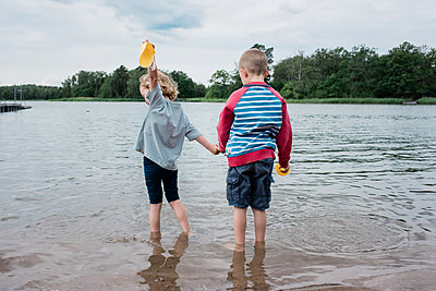 brother and sister holding hands playing at the beach on vacation - p1166m2129952 by Cavan Images