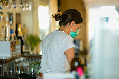 female barista at work wearing surgical portection face mask to - p1166m2201356 by Cavan Images