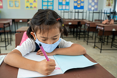 Kids wearing mask protect and safety from corona virus in classr - p1166m2212727 by Cavan Images