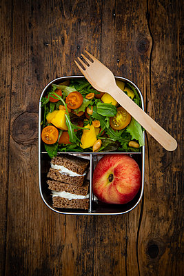 Directly above shot of vegetarian meal with fork in lunch box on wooden table - p300m2144352 by Larissa Veronesi