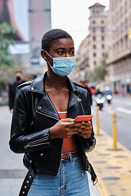Young woman wearing protective face mask using mobile phone while standing in city - p300m2250156 by Alvaro Gonzalez