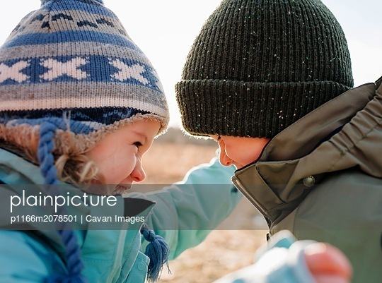 brother and sister laughing together having hun playing outdoors - p1166m2078501 by Cavan Images
