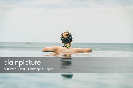 Rear view of woman in infinity pool, Koh Lanta, Thailand - p300m2166284 by Christophe Papke