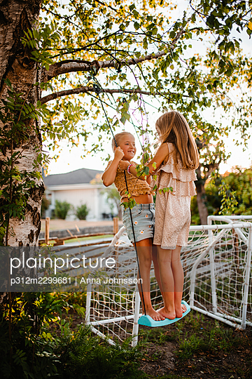 Girls swinging in garden - p312m2299681 by Anna Johnsson