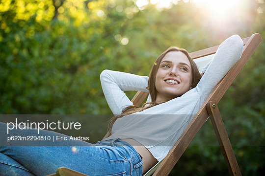 Smiling young woman with hands behind head leaning on chair - p623m2294810 by Eric Audras