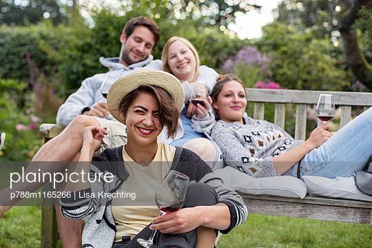 Freunde im Garten genießen Rotwein - p788m1165266 von Lisa Krechting